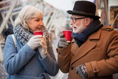 Glad mature man and woman warming up by hot drink outside. Happy old married couple is drinking mulled wine while standing outdoor in winter. They are looking at Stock Photos