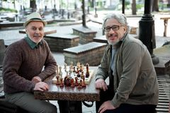Glad mature pensioners relaxing near chessboard in park royalty free stock image