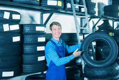 Glad mechanic man standing with new car tires Royalty Free Stock Photo