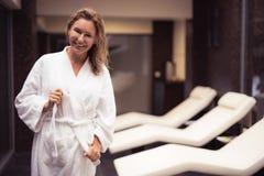 Glad mellersta åldrig kvinna med vått hår som binder badrockbältet royaltyfri fotografi