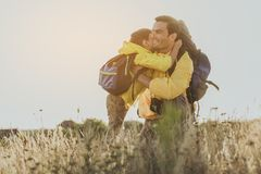 Happy son showing his love. Glad men with backpack sitting on one knee on grass in front of his son embracing him Stock Images