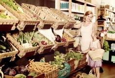 Glad moder med dottern som shoppar olika veggies Arkivbild