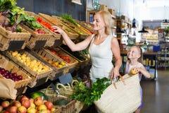 Glad moder med dottern som shoppar olika veggies Royaltyfria Bilder