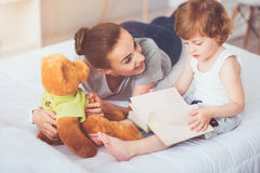 Glad moder som undervisar hennes son att läsa fotografering för bildbyråer