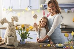 Glad mother and child hugging in festive cuisine. Portrait of happy mom and daughter standing in embrace in the kitchen that is decorated for the easter Stock Photo