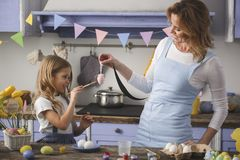 Glad mother and child preparing for holiday. Remember traditions. Happy mom and daughter colorizing easter eggs in the kitchen Royalty Free Stock Photography