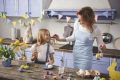 Glad mother and child spending time in the kitchen. Enjoyed mom and daughter standing in the kitchen and readying easter eggs. They are looking at each other Royalty Free Stock Image
