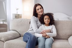 Glad mother and daughter siting on the couch. My dear daughter. Beautiful content young dark-haired women smiling and hugging her daughter while sitting on the Royalty Free Stock Photo