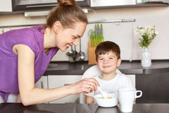 Glad mother feeds her little male child with spoon, gives delicious porridge and tea, promises to go for walk after dinner, sit at. Kitchen interrior. Smiling royalty free stock photos
