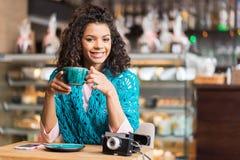 Glad mulattflicka som dricker kaffe i kafeteria royaltyfria foton