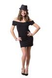 Glad nätt flicka som bär den svarta klänningen och klassikern Royaltyfri Fotografi