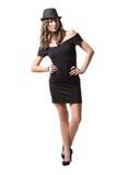 Glad nätt flicka som bär den svarta klänningen och klassikern Arkivfoto