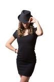 Glad nätt flicka som bär den svarta klänningen och klassikern Arkivfoton