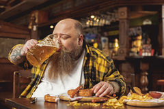 Glad obese male tasting alcohol in pub Royalty Free Stock Photography