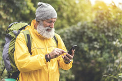 Glad old traveler looking for location with help of cellphone Stock Image
