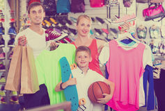Glad parents with boy in sport store. Glad parents with boy in school age shopping clothing in sport store Royalty Free Stock Photo
