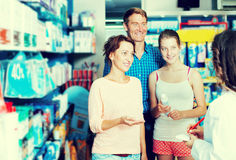 Glad parents with daughter teenager talking to pharmacist. Portrait of happy parents with daughter teenager talking to pharmacist in drug store stock photos