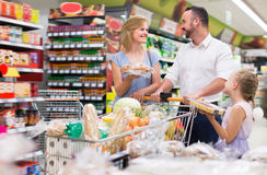 Glad parents with kid shopping in hypermarket. And having full cart stock photos