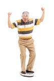 Glad pensionär som mäter hans vikt Arkivfoto