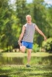 Glad pensionär som sträcker hans ben i en parkera Arkivfoto