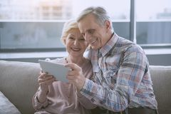 Glad pensioners resting in living room. Pleasant pastime. Elderly wife and husband sitting in hug and looking at gadget with satisfaction Royalty Free Stock Images
