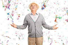 Glad pensionär i en grupp av konfettibanderoller Arkivbild