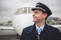 Glad pilot locating opposite plane. Side view beaming young aviator situating opposite aircraft on street. Labor concept Royalty Free Stock Photos