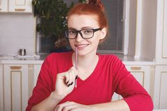 Glad pleasant looking ginger female writer holds pencil, being satisfied as has inspiration for writing, generates good ideas in h. Er mind, sits at kitchen stock photography