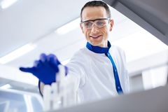 Glad pleasant scientist choosing container. I found it.Happy cheerful male scientist deciding about medication while wearing medical glasses and holding Royalty Free Stock Photography