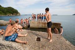 Glad pojke- och flickabanhoppning in i havet från den gamla pir Royaltyfria Bilder