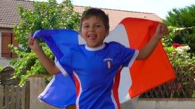Glad pojke som hoppar med en fransk flagga i hans händer arkivfilmer