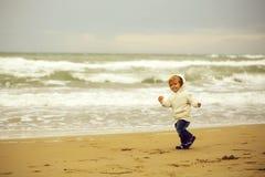 Glad pojkespring p? stranden arkivbilder