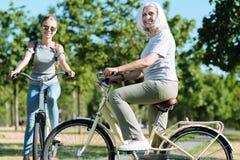 Glad positiv kvinna som rider en cykel arkivbild