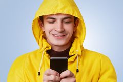 Glad positive male wears yellow anorak and hood, types messages on smart phone, uses free internet connection. Handsome man uses m Royalty Free Stock Photography