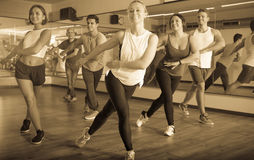 Glad positive people learning zumba steps. In dance hall Stock Photography