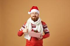 Glad rödhårig man med det iklädda skägget en röd och vit tröja med hjortar, en vit stucken halsduk och en hatt av jultomten arkivbilder