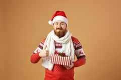Glad red-haired man with beard dressed in a red and white sweater with deer, white knitted scarf and a hat of Santa stock images