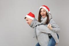 Glad rolig parflickagrabb i scarves för tröjor för röd Santa Christmas hatt som gråa isoleras på grå väggbakgrund, studio arkivfoton