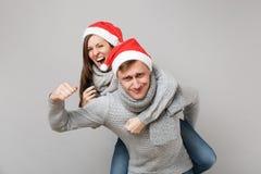 Glad rolig parflickagrabb i scarves för tröjor för röd Santa Christmas hatt som gråa isoleras på grå väggbakgrund, studio arkivbilder