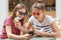 Glad satisfied female companions being focused ino screen of modern cell phone, watch interesting video online, connected to wirel. Ess internet, eat cold ice royalty free stock photos
