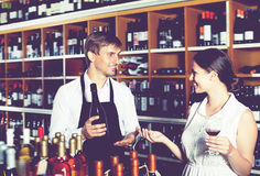 Glad seller man giving sample taste of wine. Glad seller men wearing apron giving sample taste of wine in glass to women customer in wine store Stock Photo