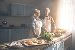 Happy old married couple baking buns in kitchen royalty free stock photography