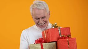 Glad senior male holding present boxes in hands, holiday preparation, surprise. Stock footage stock footage