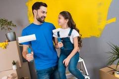 Glad skäggig fader och litet dotterplan som målar väggen med rullar i guling arkivbild