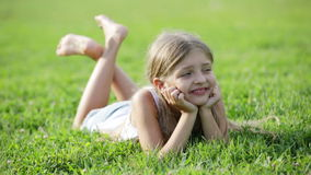 Glad small girl lying on green grass in park. Glad small girl in elementary school age lying on green grass in park stock video