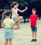 Glad small kids playing with jumping rope. Glad small kids in school age playing together with chinese jumping rope outdoors. Focus on boy Royalty Free Stock Photography