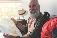 Glad smiling elder tourist holding navigation paper. Joyous mature bearded man is using man and looking at camera with smile. He sitting in waiting hall Royalty Free Stock Images