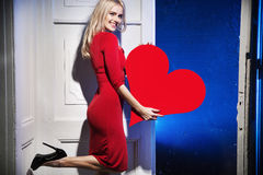 Glad and smiling woman holding a heart Stock Photo