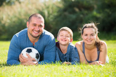 Glad son and parents lying in football field Royalty Free Stock Image