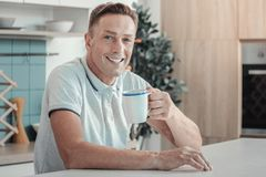 Glad stilig man som ler och dricker te arkivbilder